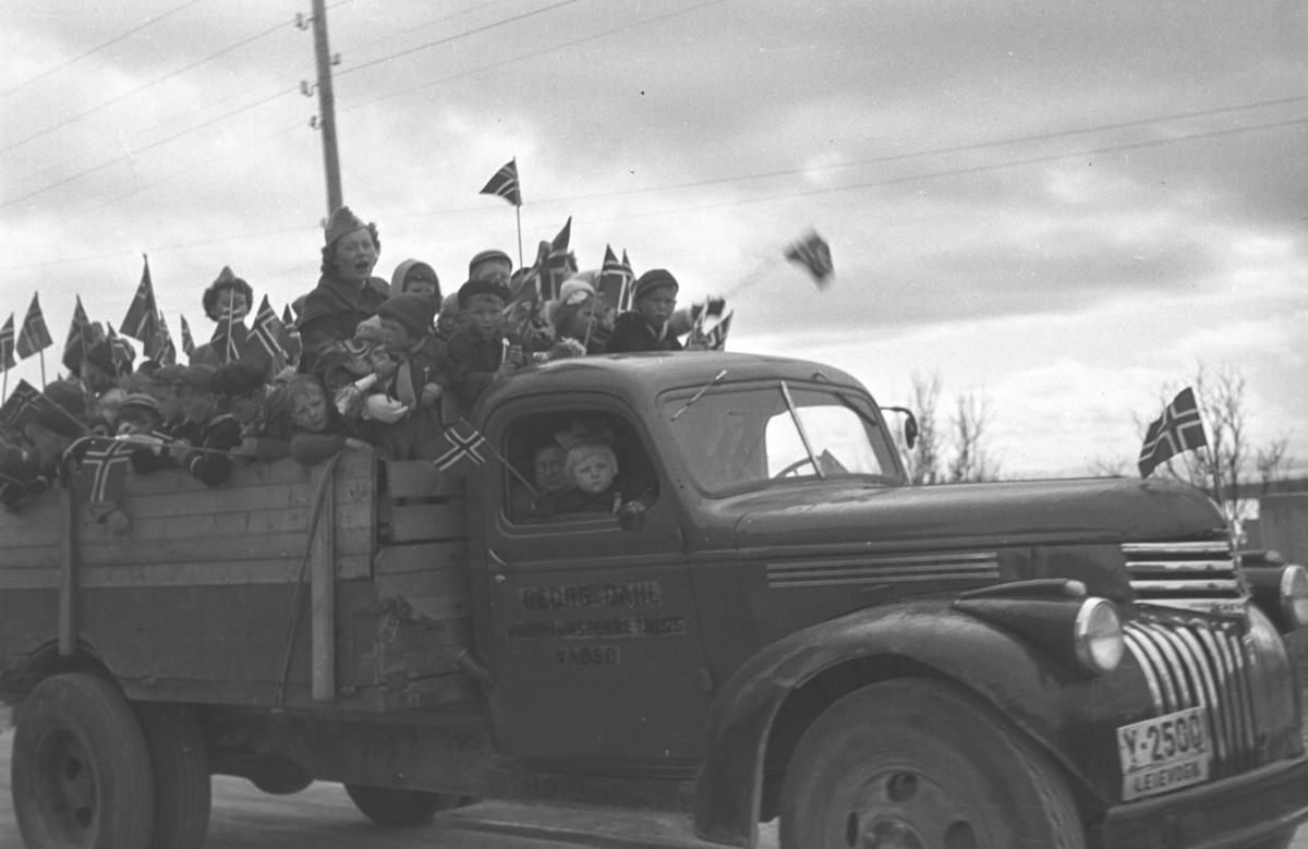 17. mai-feiring i Vadsø. Lotter er satt til å passe barna som er samlet på lasteplanet til en Chevrolet 1946-47 mod. mens de vinker med norske flag.