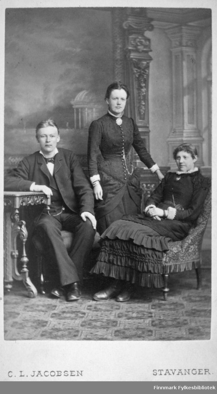 Portrett av tre personer, en mann og to kvinner. Mannen til venstre på bildet har en mørk dress, hvit skjorte, sløyfe i halsen og mørke sko på seg. Han sitter i en stol og hviler høyrearmen på et lite bord. Damen i midten står og har en mørk kjole på seg. En brosje i halsen og en lang kjede som går fra halsen og nedover brystet. Damen til høyre på bildet sitter i en stol og har en mørk kjole på seg. En hvit krage ses rundt halsen hennes. På gulvet ligger et mønstret teppe og bak dem henger et stort maleri på veggen. Portrettet er tatt hos C. L. Jacobsens atelier i Stavanger.
