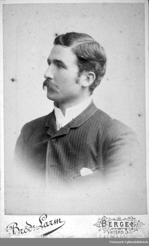 Portrett av en mann iført en mørk dressjakke med tynne striper. Den hvite skjortekragen ses i halsen hans og fra brystlomma stikker noe lite og lyst opp.