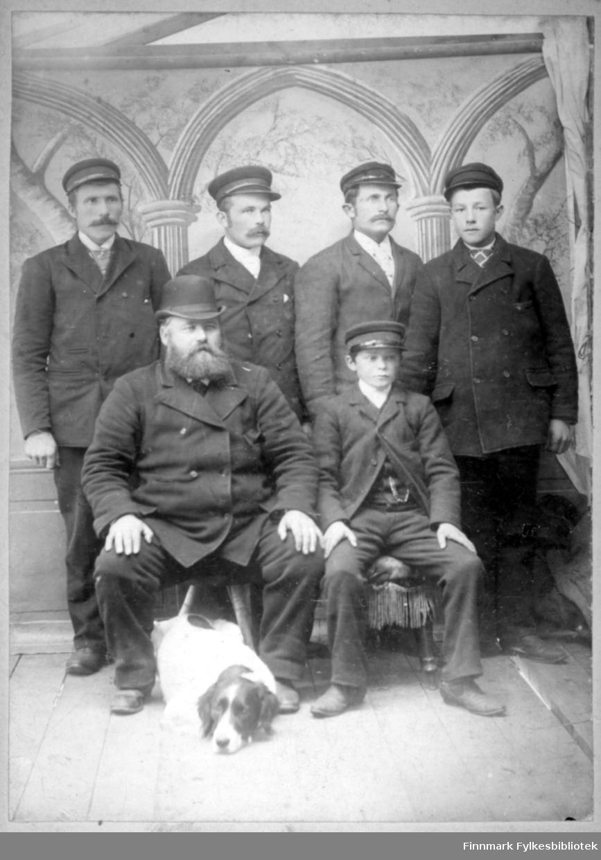 Portrett av fem menn i mørke dresser. Fire har mørke luer med skjerm, mens en har mørk bowlerhatt. De to foran på bildet sitter og på gulvet ligger en hund. Gulvet har brede planker og veggen bak har tapet med mønster.