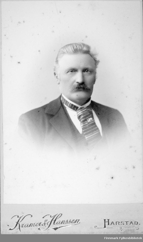 Portrett av en mann. Han har en mørk dressjakke, hvit skjorte og et stripete slips knytt utenpå kragen.