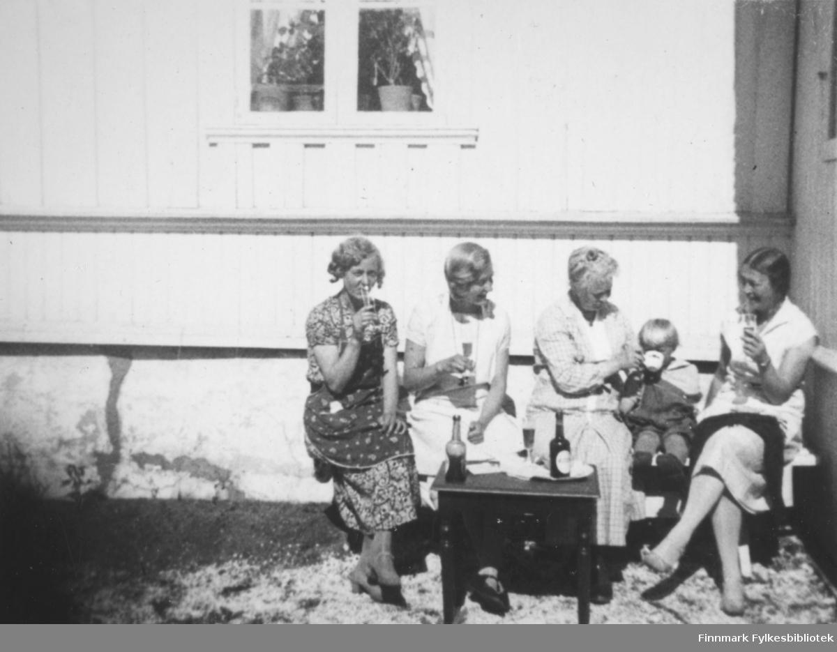 Fire damer og et barn sitter i solveggen. Damen til venstre har en mønstret, kortermet kjole på seg. Damen ved siden av har en hvit/helt lys kortermet kjole. Hun ved siden av barnet har en rutet kjole og holder en kopp opp mot barnets munn. Barnet har ganske mørke klær og damen til høyre ar en hvit kortermet bluse og et litt mørkere skjørt. Et lite mørkt bord står foran dem med et vinglass og to flasker oppå. Tre av damene holder hvert sitt vinglass i hendene. Veggen bak dem er hvit og et to-delt vindu står øverst på bildet. I vinduet ses gardinger og to-tre potteplanter.