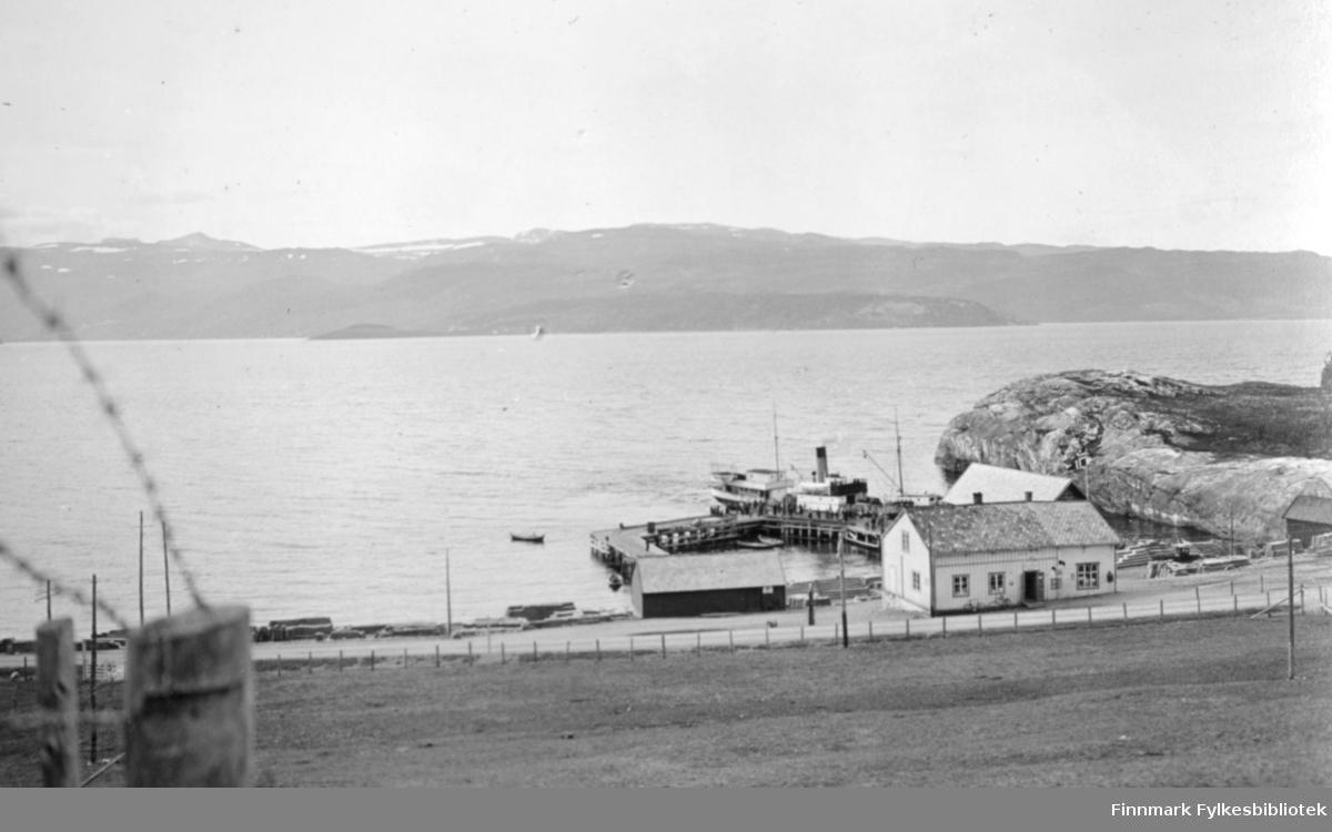 Bossekop en sommerdag. En vi går på tvers gjennom hele bildet og to havnebygninger ligger bak den, begge med skifertak. Det nærmeste er hvitt med mange vinduer. Til venstre for dem ligger en mindre, mørk bygning og til høyre på bildet, et lite bygg. Ved siden av det stikker et berg/nes ut i Altafjorden. En kai midt på bildet og en båt ligger fortøyd der med endel mennesker på kaia ved siden av. En liten båt ligger på sjøen til venstre for kaia. Foran på bildet er et stort, inngjerdet jorde og helt til venstre ses et par gjerdestolper med piggtråd. Små bølger ses ute på fjorden og det er ganske overskyet. På fjellene i bakgrunnen ligger noen snøflekker.