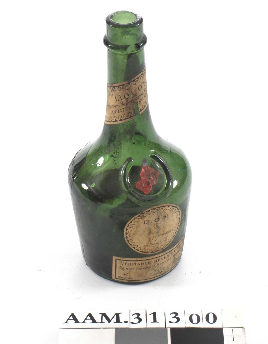 """Flaske med sirkelformet bunn, lav """"kropp"""" og lang hals. Rest av forseglingsstempel av lakk."""
