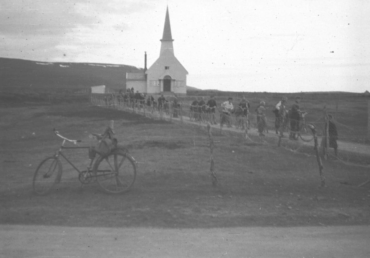 En del personer kommer ned kirkebakken, noen med sykler. Stedet er ukjent.