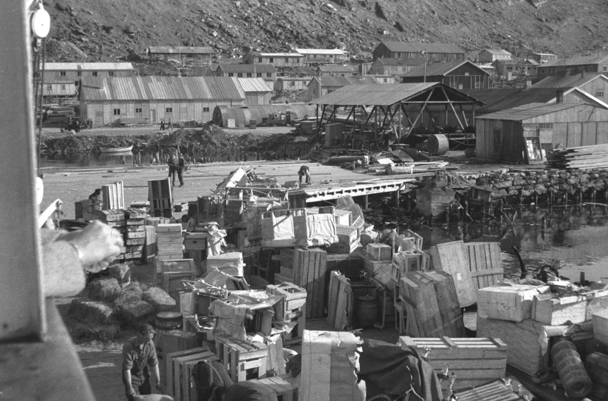 Mye bagasje og kasser, som tilhører hjemvendte evakuerte, ligger på en kai. Bildet er tatt fra Hurtigruta. Stedet er kan være Honningsvåg.