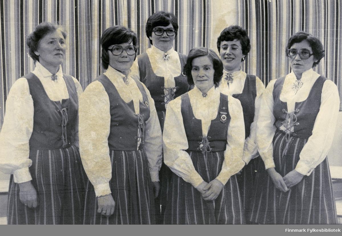 Avbildet er Vadsø damekors styre på 30 års feiringa. Bildet er trolig tatt på begynnelsen av 80-tallet. Damene er kledd i bunad, smykker og brosjer. Tre av damene har på seg briller. Bak dem kan man se gardiner. Første rekke fra venstre: Birgith Støvik, Karethe Sæther, Åse Eriksen Nygård og Ellen Roska. Bakerste rekke fra venstre: Berthine Oldernes og Gudrun (Gunne) Berg Hansen.