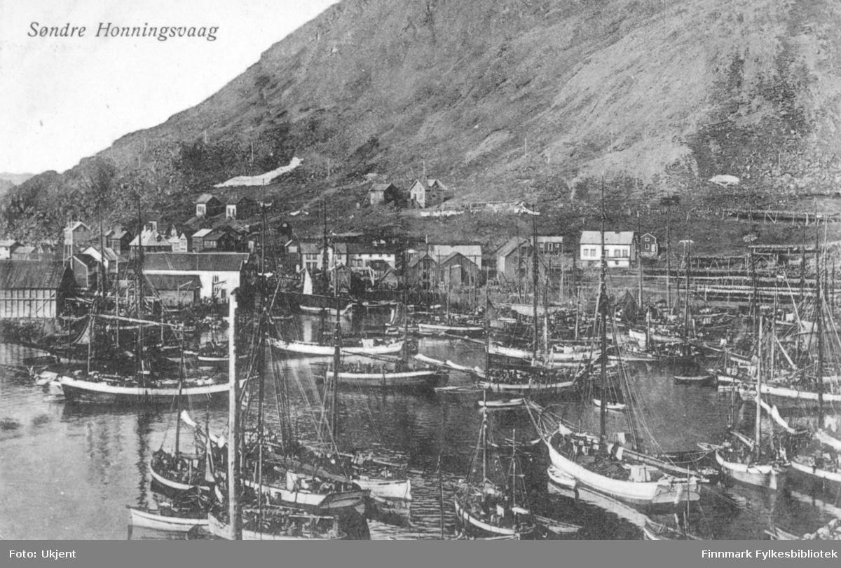 Søndre Honninsvaag som motiv på dette postkortet. På bilde kan man se en havn med flere båter til kais. I bakgrunnen ser man bygninger og fjell.