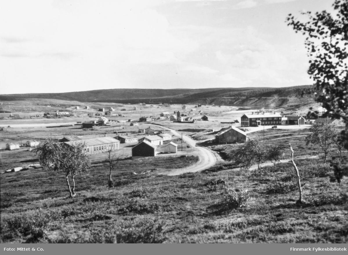 Et bilde av Kautokeino. På bildet kan man se flere bygninger og grusveier. I bakrunnen kan man se fjell.