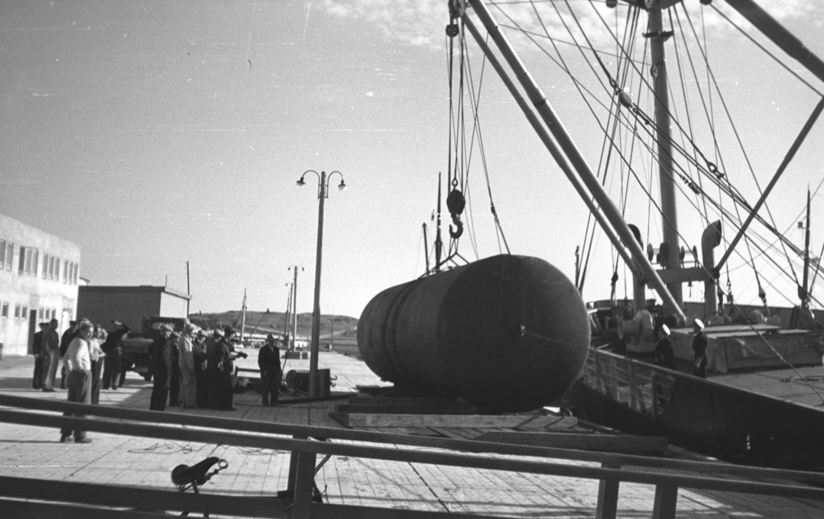Et lasteskip losser en stor tank ved kaia i Vadsø. En del personer står ved siden av tanken.