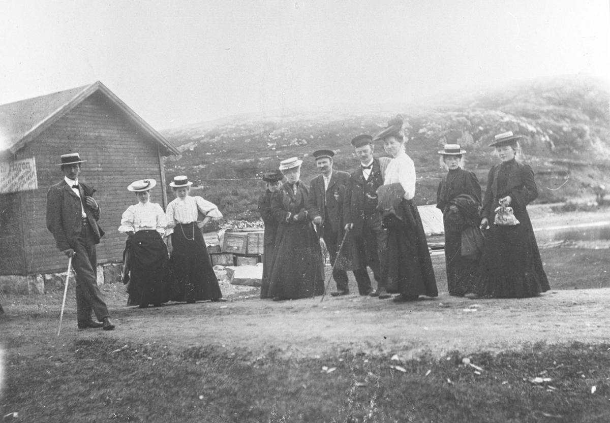 Gruppebilde av 3 menn og 7 damer trolig i Syltefjord. Deler av bygning bak gruppen på venstre side. Plakat på veggen. Tekst på plakaten er uklar. Kasser av træ bak hushjørnet. De er velstående og er kledd i finklær. Kvinnene har lange kjoler og hatter med slør.  Dem har jekka på eller med seg. Mennene har dress med sløyfer og sommerhatter. To av dem har stokk. Fra venstre Hilmar Bohne, ukjent, ukjent, Golla Fuglevik (i lys hatt med slør) og 'Jossa' Johan Nilsen.