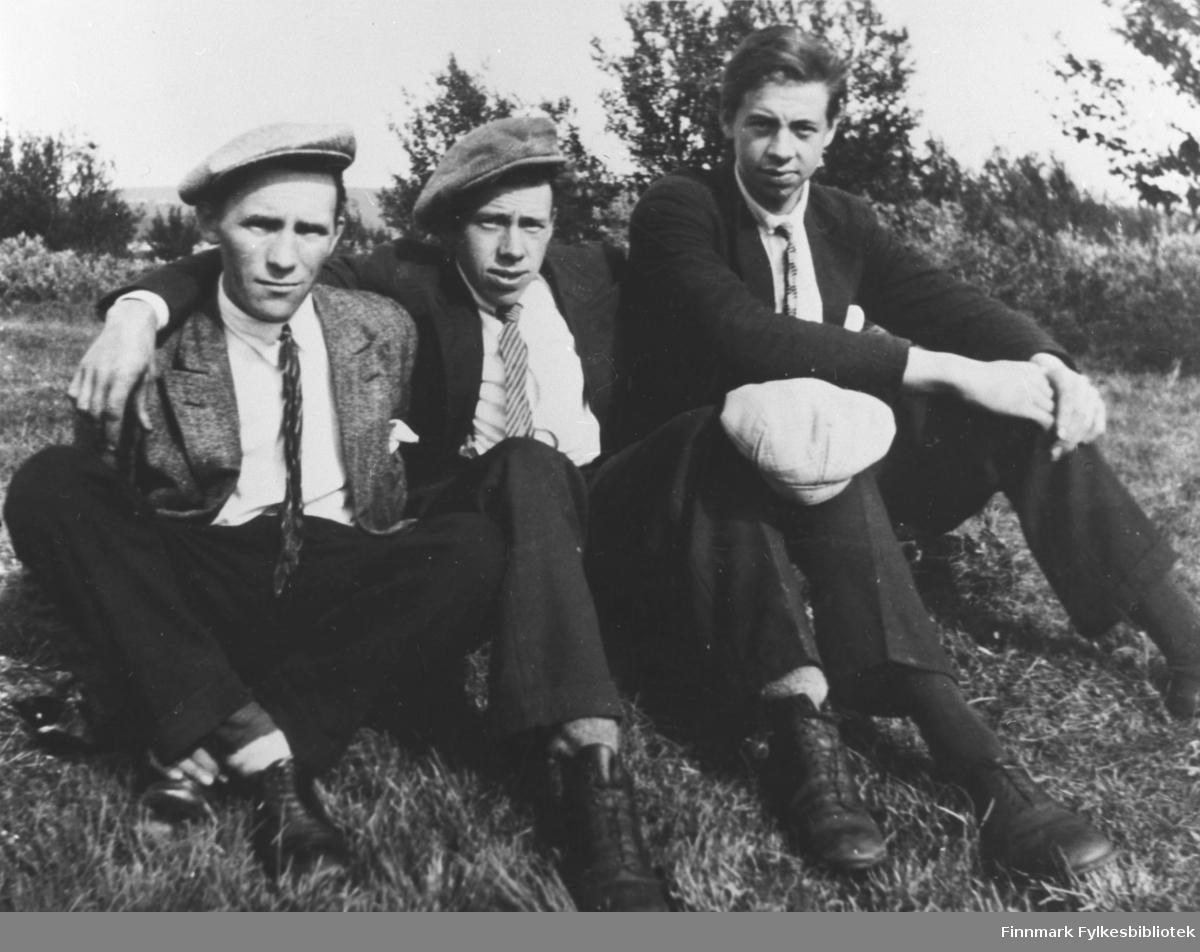 Tre unge menn; Andreas Peder Stahl, Johan Petter Store og Fredrik Waldemar Store, fotografert sittende på gresset. Mennene er kledd i dress, slips og luer. Alle tre ser rett på kamera.