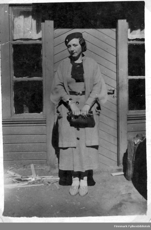 Helfigurportrett av kvinne med fin drakt, håndveske og hatt, hun står foran en dør