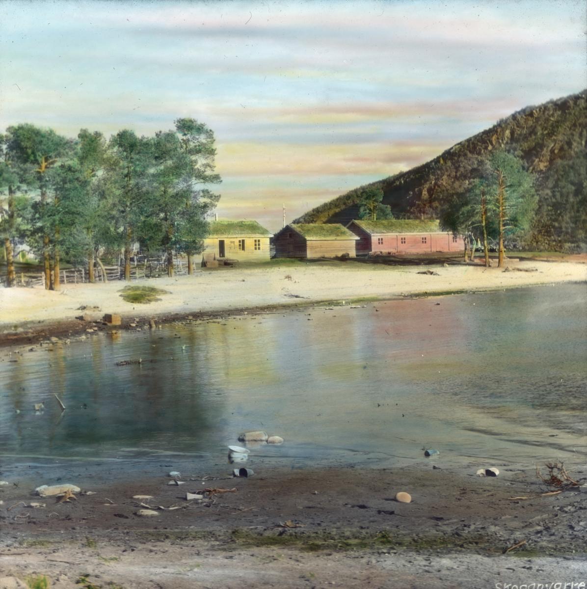 Håndkolorert dias. Tre trehus med torvtak ligger ved en strand i Skoganvarre, Porsanger.