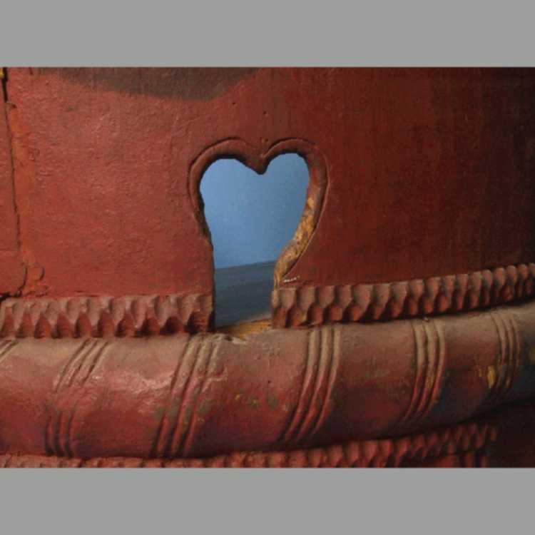 Kubbestol  av bjerk.  Meget stor, lav og bred kubbestol   med utskåret understell. Armlener. Rødmalt. Bak på ryggen malt et stort brunt hjerte med bokstaver og årstall i gråhvitt:   H S D H J O S H - 1815