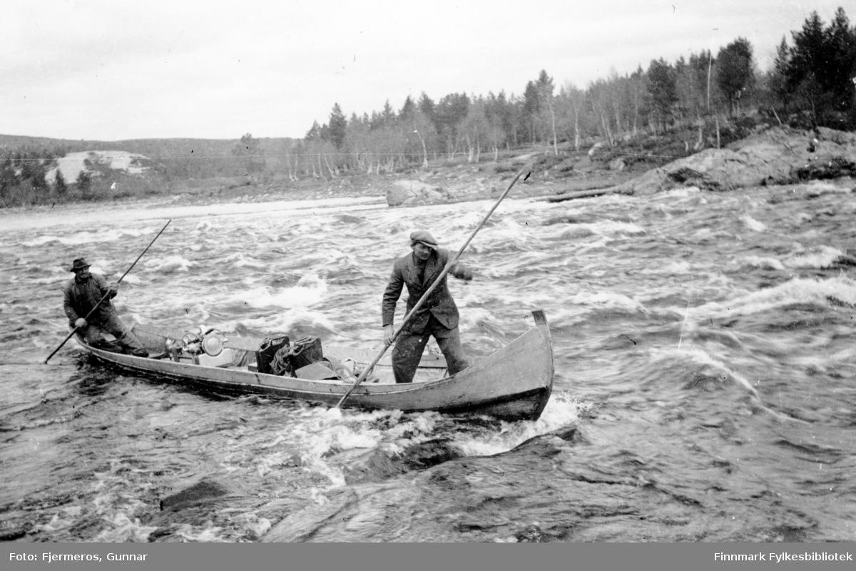 To menn staker en elvebåt. Fornavnene deres er Niilas og Àndi, sted og etternavn er ukjent, men elva er nok Karasjohka. Bildet er tatt våren 1946.