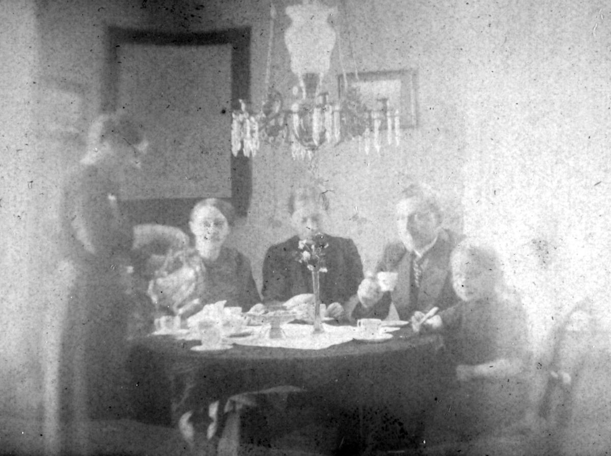 Håheim-familien i Neiden sitter rundt et bord. De fleste personene på bildet er ukjent, men mannen til høyre kan være Reidar Håheim. Han er kledd i jakke og slips. Ved siden av han sitter en liten jente i kjole. Over bordet henger en lysekrone.