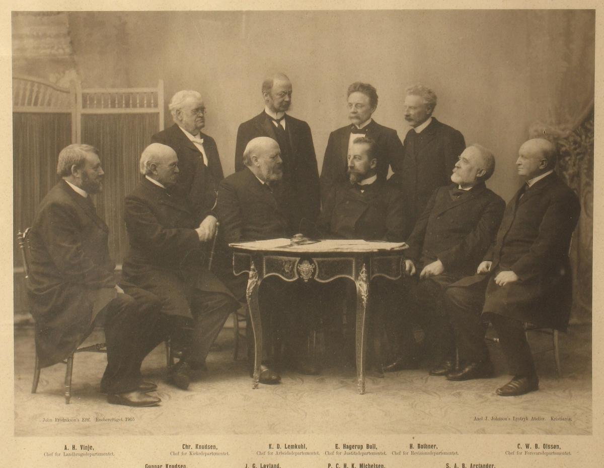 Gruppeportrett av den norske regjering i 1905,  10 menn samlet rundt et bord. 6 sitter på stoler, 4 stående bak. De 5 på høyre side ser mot venstre, og vise versa. Navnene er trykt i bildets nedkant.