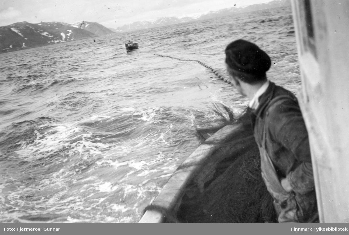 En mann står på hekken til en fiskeskøyte som har nota ute, og en lettbåt ligger på vannet i bakgrunnen. Bildet er tatt øst for Nordkapp våren 1948. Personer, sted og båt er ukjent.