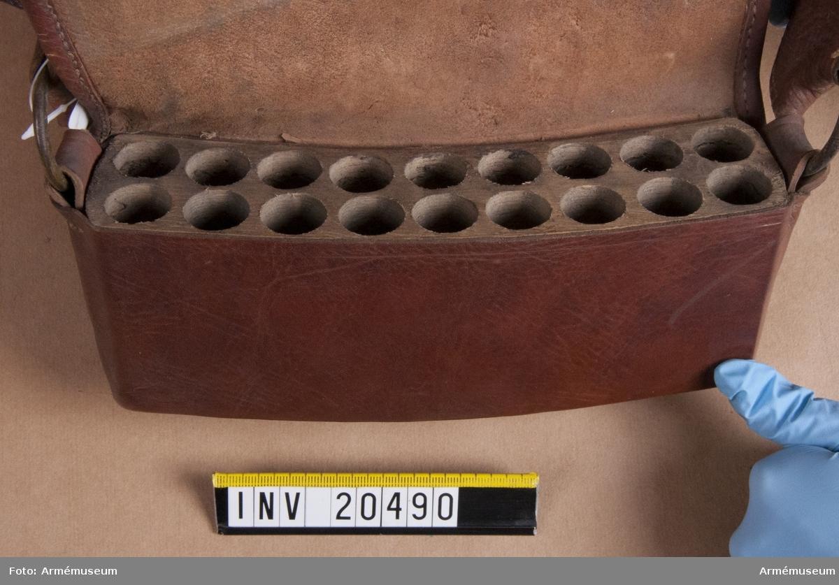 Grupp C II. Patronkök, menig, husarer, Ryssland, 1802. Består av en träbit i vilken det finns arton fördjupningar för patroner. Den är beklädd med brunt läder. På nedre finns en läderknapp för att stänga väskan.