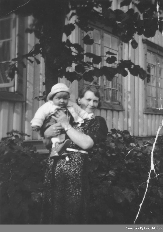 En kvinne holder et lite barn i armene. Sted og personer er ukjent, men det kan være Ragnfrid Elise Karlsen med sønnen Arne Martin.