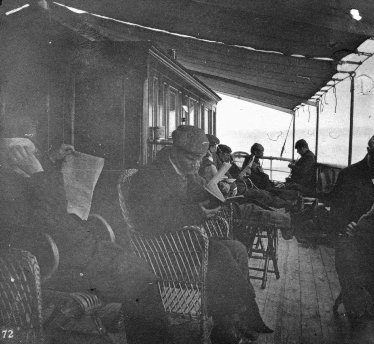 """""""Still-leben."""" Flere menn sitter på dekk og leser avis eller bok."""