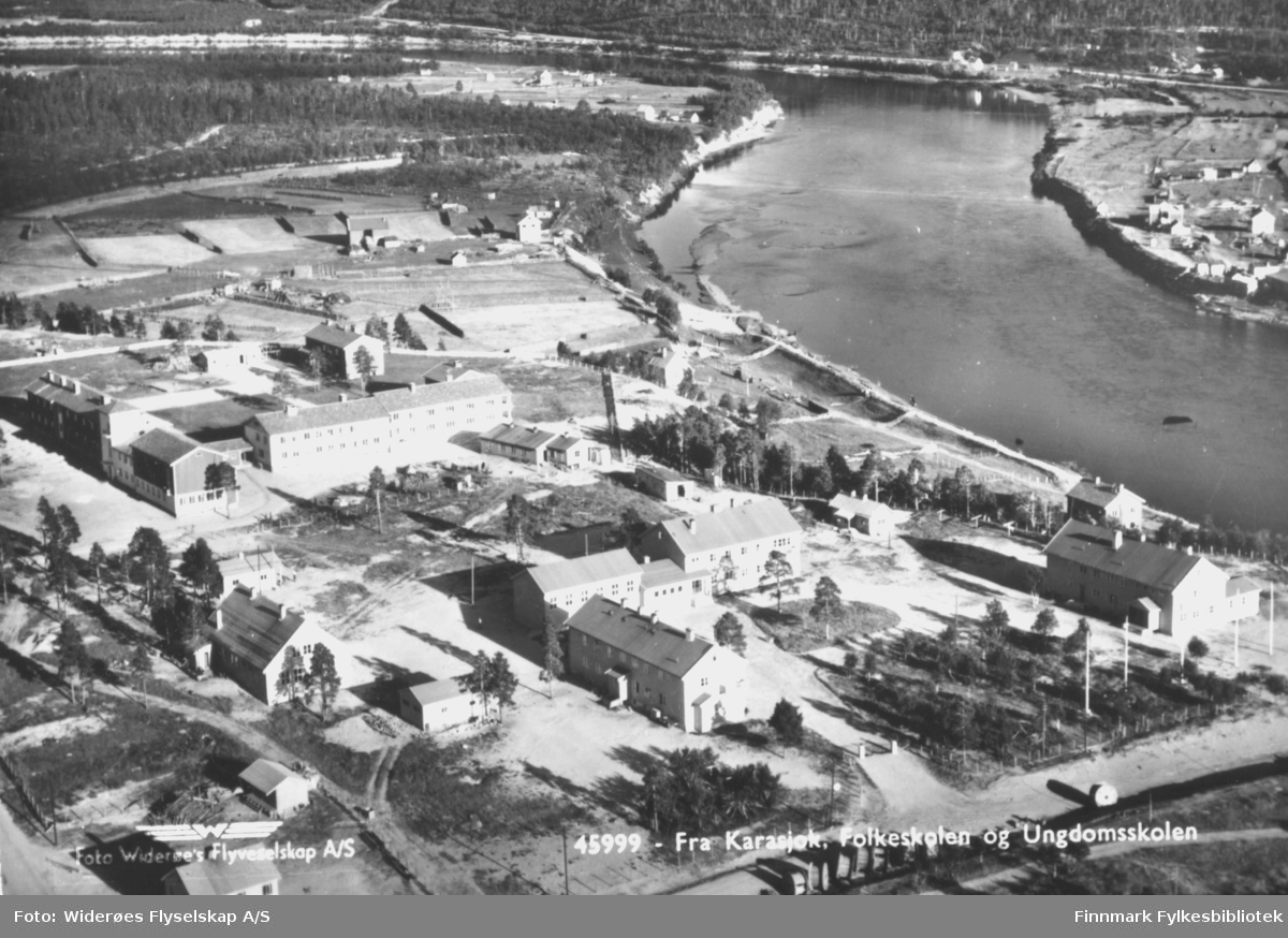 Flybildet av Karasjok. Påskrift på postkortet:'Fra Karasjok. Folkeskolen og Ungdomsskolen'. På bildet kan man se flere andre bygninger, veier og stolper.
