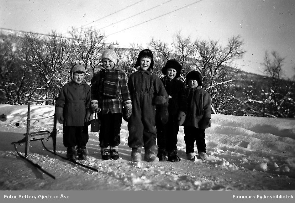 Fem barn poserer til fotografen på en veikant i en solig vinterdag i 1955/56. Jentene og guttene er kledd i vinterjakker, luer og votter. Noen av dem har komager på seg. Ved sidan av dem står en spark. Fra venstre: Åstrid Betten, Bjørn Ottar Betten, Oddvar, Kjell og Torill Betten. Åshild, Oddvar og Kjell er søsken. Alle unger er søskenbarn til hverandre.