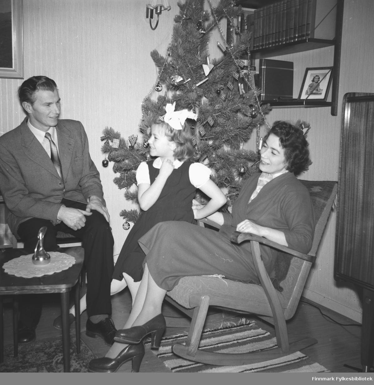 Familieportrett av Eino, Turid Lillian og Jenny Drannem ved juletre, tatt i jultiden i stua
