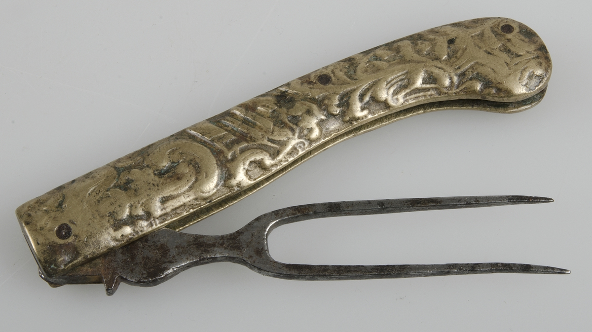 Fällgaffel, skaft av gjuten mässing med rokokoornament, tvåhornad gaffel av järn. Hopfällbar.