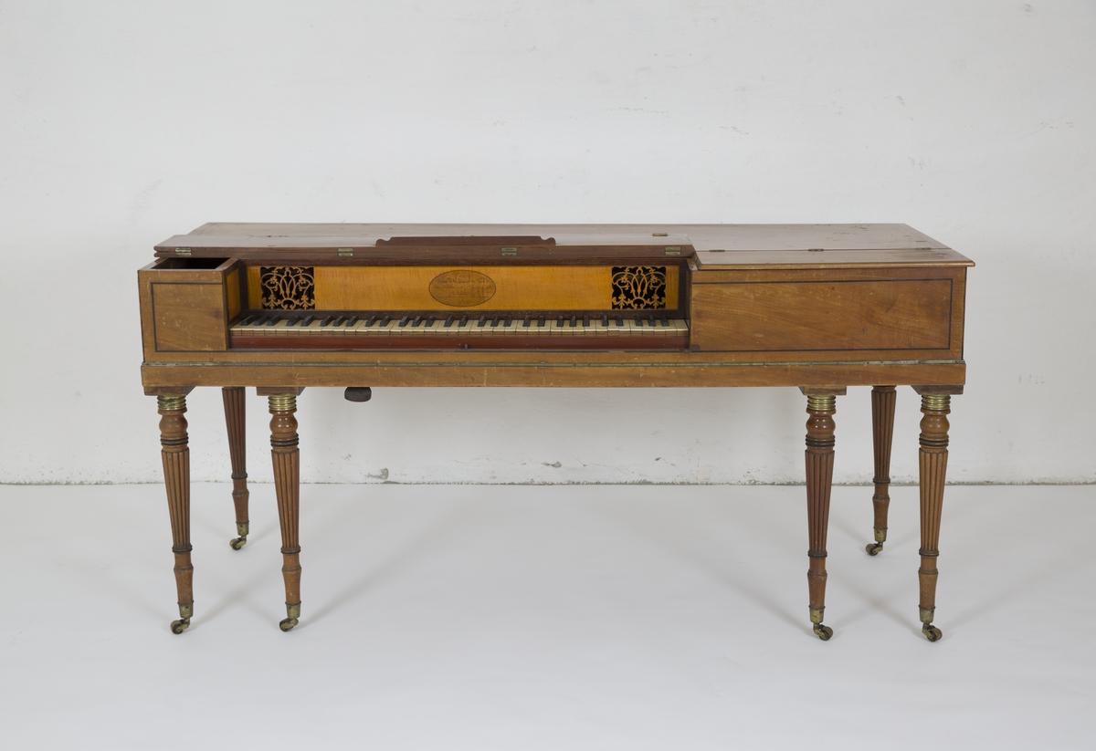 Taffelpiano med seks dreide ben med hjul. Skåret ornamentikk ved tangenter og på innsiden. Sammenbretbart notestativ.