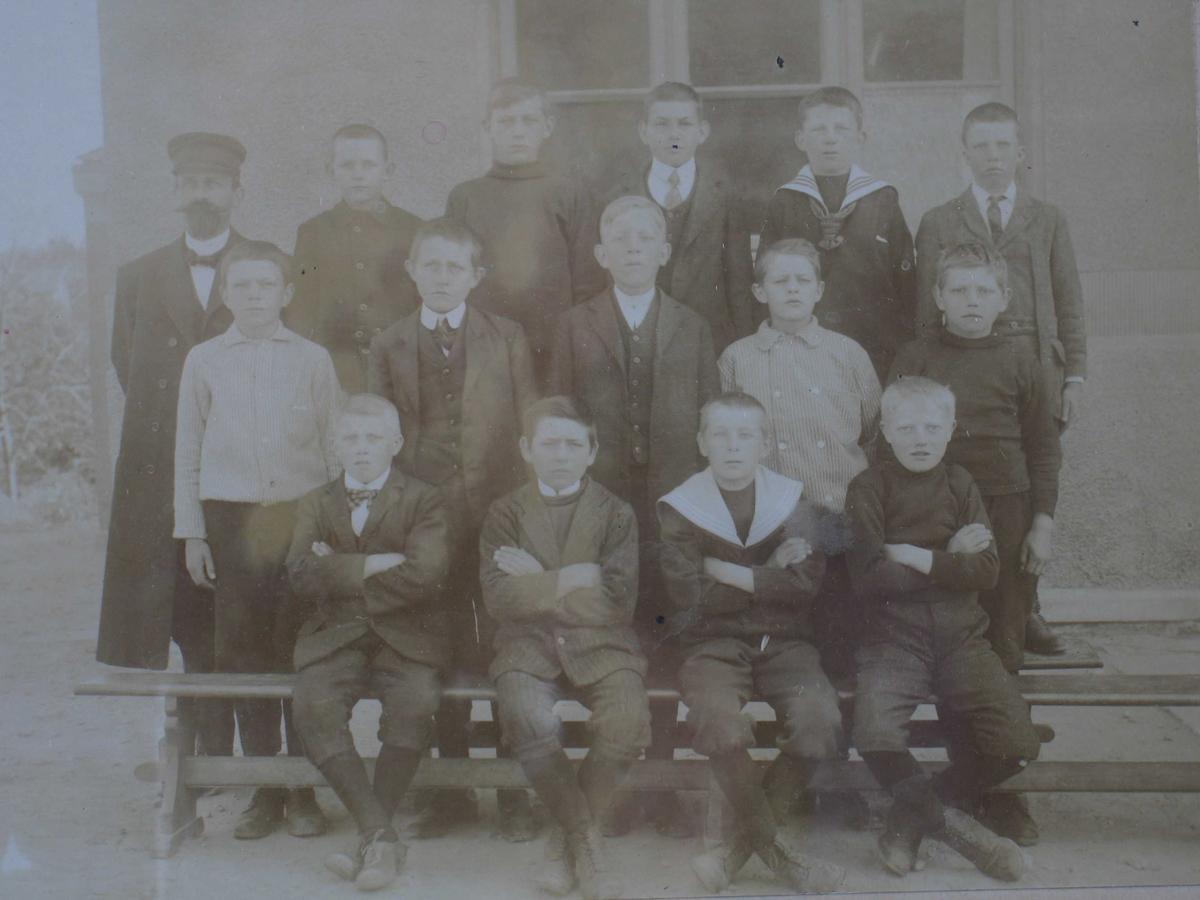 Fotografi tatt utendørs foran vindu, av gutteklasse og deres mannlige lærer. Bildet er tatt foran den gamle skolen i strandstedet.