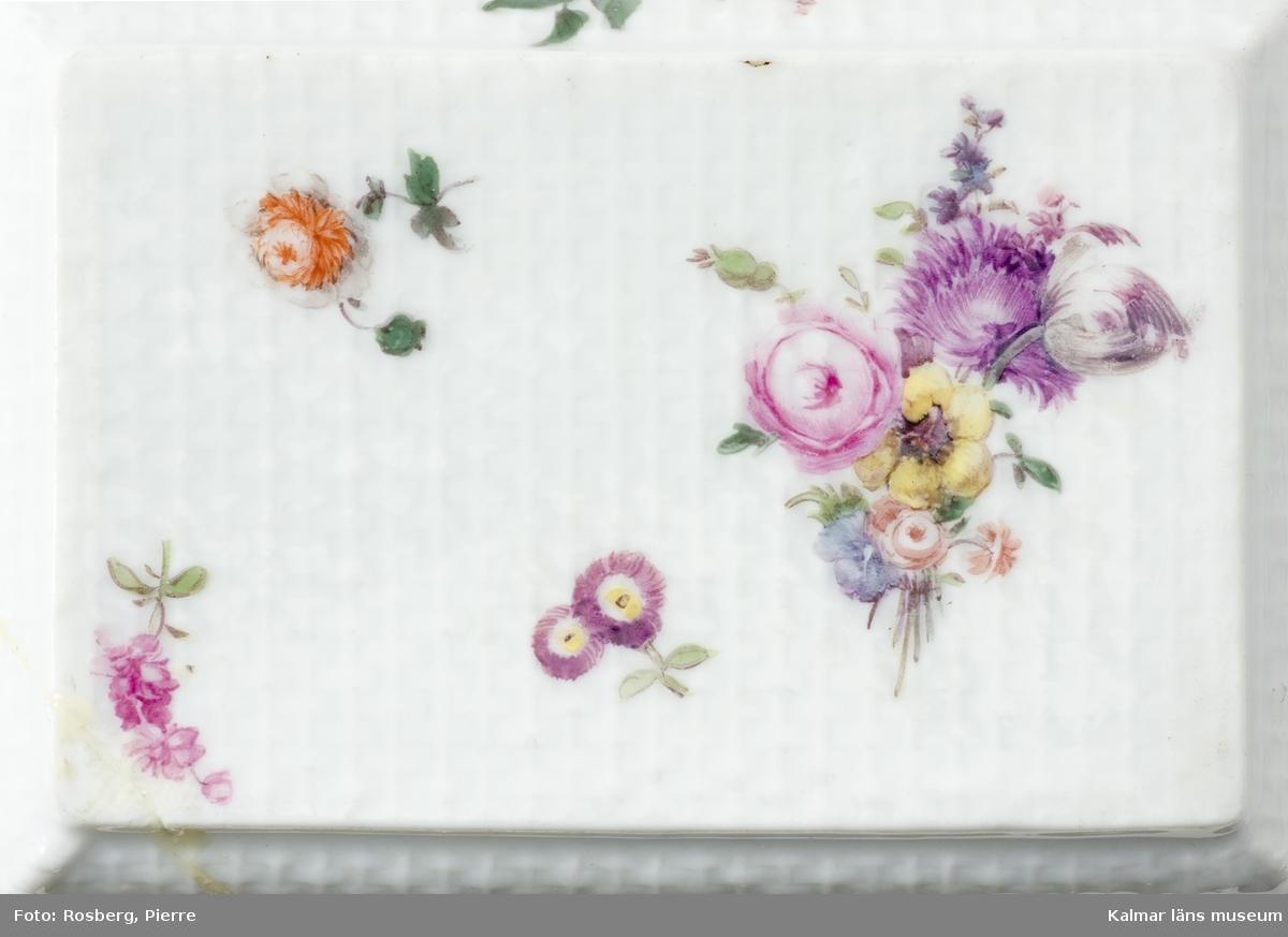 KLM 6720 Dosa, av porslin. Rektangulär form. Av vitt porslin med många blomsterkvistar i flera färger, på alla yttersidor, porslinsytan ska påminna om vävd textil. På lockets insida en stor blomsterkorg, troligen ett emaljmåleri. Beslag och gångjärn av metall.