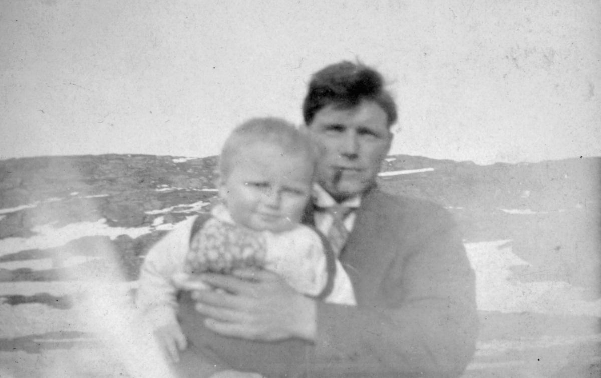 En mann holder et barn i armene. Sted og personer er ukjent, men bildet er muligens tatt i Kvalsund kommune.