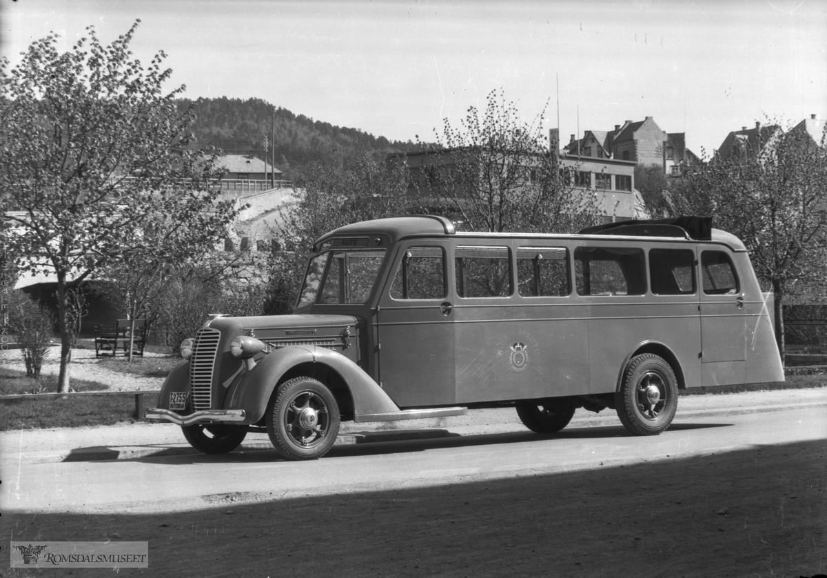 Buss fra Hjelset Auto med reg nr T-2755..T-2755 var en Diamond T, 1936-modell turistbuss med sammenfoldbart tak. Karosseriet ble påbygd av Ivar Røvik Karosserifabrikk, Røvik, og hadde bygg nr. 39. .Hjelset Auto ble startet i 1929 av Torstein Vorpenes, Hjelset, med ruter Hjelset-Molde. I 1943 ble Hjelset Auto overtatt av Haukebø & Rødseth, som også drev Aarø Automobilselskap. Hjelset Auto bygde ut lokalruter rundt Molde, Mordalruta fra 1946 og Ringbussen fra 1953. Trafikken på disse rutene vokste betraktelig utover 1950- og 1960-tallet. .I 1973 ble disse busselskapene slått sammen med Batnfjord Auto og Kleive Auto, og fikk navnet Molde Bilruter. Dette selskapet drev disse rutene til slutten av 1990-tallet. I 1972/1973 ble det bygd nytt anlegg for bussene i Fannestrandveien 71. Denne virksomheten har hatt tilhold der i alle år siden. I dag driver Vy Buss bussrutene, og Wist Last og Buss står for verksteddriften..I Romsdalsgata i bakgrunnen ser vi Ford-forhandleren Haukebø & Rødseths sin funkisbygning delvis skjult av løvverket.