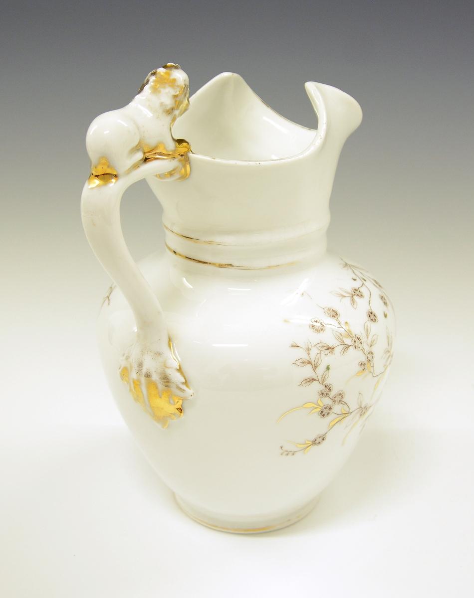 Sjokolademugge i porselen. Liggende løve modelert øverst på hanken. Hvit glasur. Dekorert med gull og blomstergren i brunt. Håndkolorert ståltrykk. Modell: 999. Dekor: 1566.