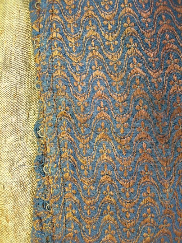 """Livstycke från Mark, Västergötland. Mönstervävt sidentyg med blå bomullsvarp med brunt silkeinslag som binder i satin samt flotterar i mönster tillsammans med ett extra mönsterinslag i turkost silke. Mönster: """"Fransk lilja"""" samt bågform på tvären. Sidsöm, rundad halsringning. Sydd med mörk bomullstråd. Knäpps med 11 st hyskor och hakar i framkanten. Under hyskorna slå i samma tyg som livstycket. Insnitt 15,5 cm långt från midjan till bysten. Livstycket är fodrat med naturfärgat svart-vitt bomullstyg, tuskaft. Påsytt formskuret skört i midjan, 12 cm långt, av rutigt bomullstyg i brunt och blått.  Framkanten rundad, i sidan lagda veck. Söm mitt bak. Skörtet är fodrat med blått och brunt bomullstyg, tuskaft. I ärmringningen ett svart tyg sytt som passpoal, ca 1 mm. Utmed hals och framkant en infodring som sticker ut 2 mm utanför kanten. Stickningar ca 8 mm innanför framkantens vikning."""