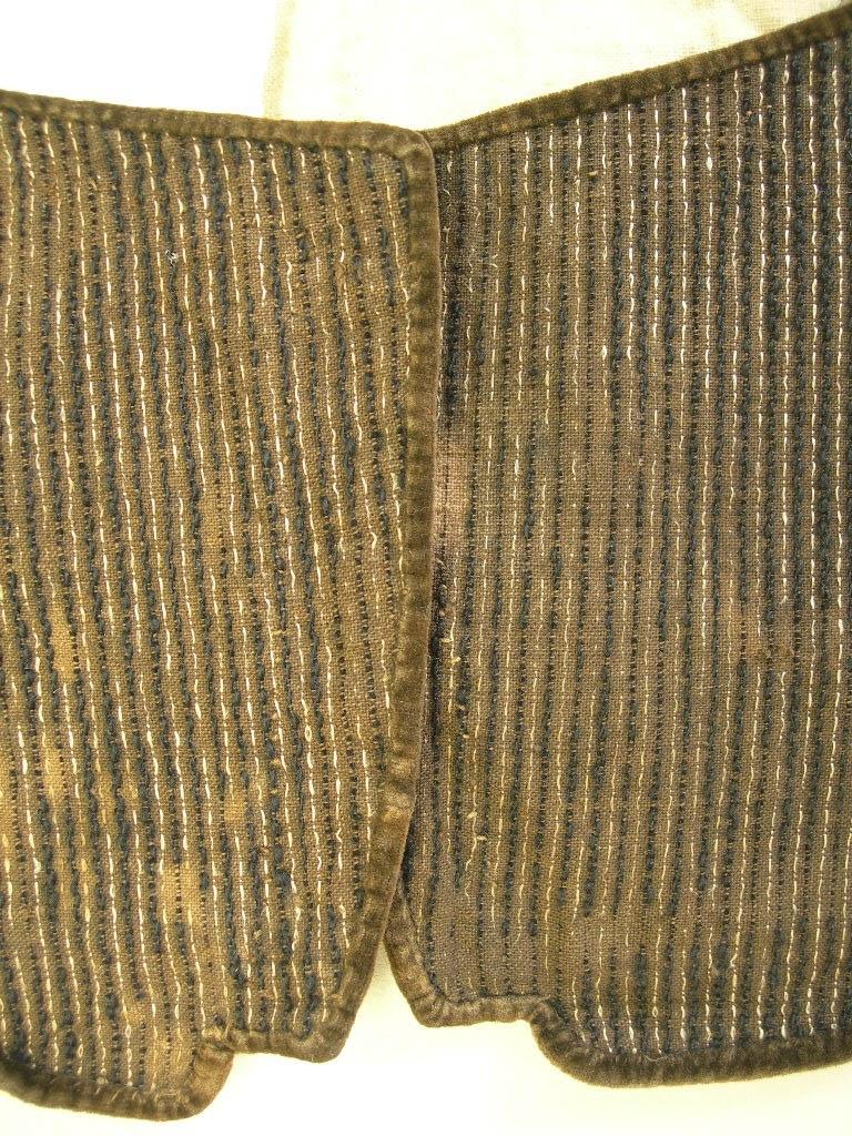 Livstycke från Marks härad, Västergötland.  Randigt med tuskaftsvävd brun botten med flotteringar i svart ullgarn och ofärgad bastfiber. Sydd med brun lintråd. Ca 1,5 cm brett uppvikt skört, fastsytt bak med förstygn. Vikningen sluttar fram mot framkanten. Två skörtflikar bak. Skörtet fodrat med likadant tyg som i själva livstycket. Urringningens nederkant, framkant och skörtets kant kantat med brun bomullsammet. Ingen knäppning. Foder av ofärgad bomull, tuskaft; i axelpartiet två kypertvävda tyger, ett i lin och ett i bomull. Ficka, 8 x 9 cm, påsydd på höger insida, brunrutigt tyg med rutor i rött, blått och gult. Påsydd bomullslapp, 8 x 4,5 cm, märkt med  No. 10 N. Livstycke, Äg. Herr Alfred Andersson, Storgården, Gunnarsjö.