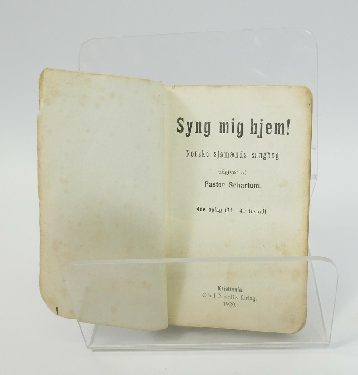 Rektangulær bok med rødt omslag.   Påskrift, trykt på omslaget:  Norske sjømænds sangbog // SCHARTUM // SYNG MIG HJEM!