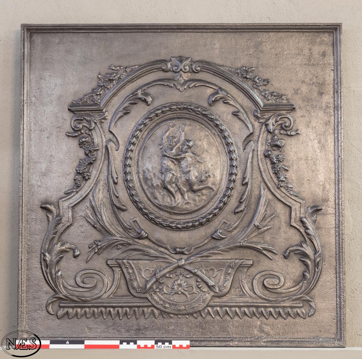 Kaminplate. Kvadratisk i formen. Støpt i åpen form. Hele platen er rammet inn med en enkel profilert list. Motivet er symetrisk oppbygget i akantusstil med en medaljong i midten. Medaljongen er rammet inn med laubærblader og dansende muser i midten.
