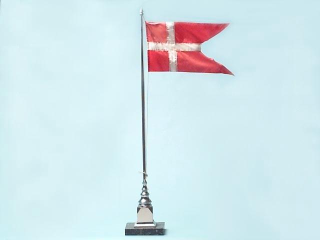 Bordsflagga. Vänortsgåva. Flaggstång i silverfärgad blank metall. Står på marmorsockel. På sockeln finns en platta med följande inskription: GLOSTRUP SOOGNERAAD, 13.9.1947. Under sockeln finns påklistrad lapp med följande text: 49. Sogneraad = Kommunalnämd (1947, Sttme § 172). I toppen hänger dannebrogen, vitt kors på röd botten.