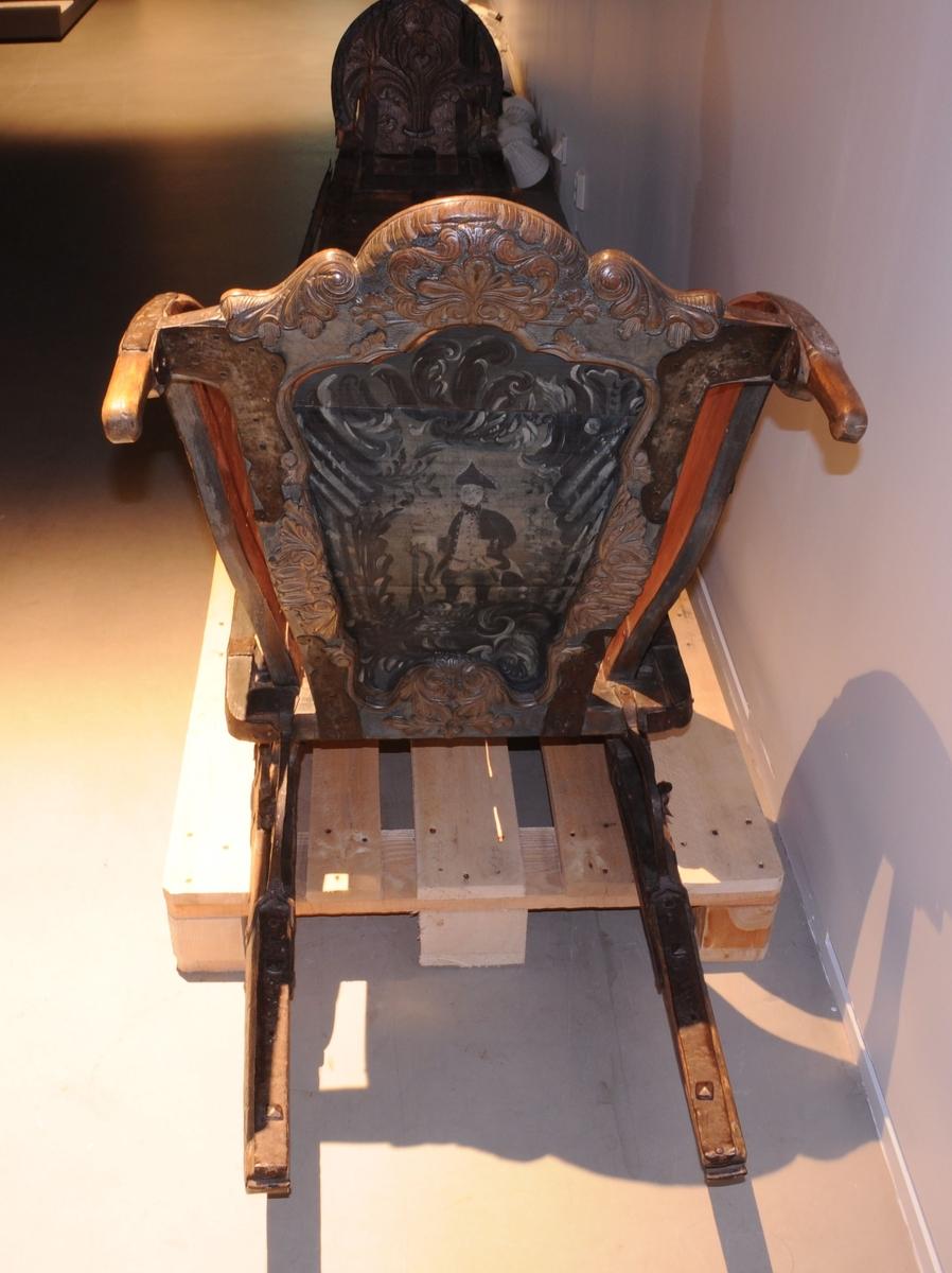 Spisslede av tre, nærmere bestemt en barokkslede. Det er en spalte mellom sidevangene og ryggstøtten. På sidevangene og ryggstøtten er det rammeverk med maling på innsiden. Motiv på malingen av offiser med gevær og sverd på baksiden. Rammen har skåret dekor av barokkformer. På sidene av sleden er det bøyler av jern. Håndtakene er utledet fra sidevanger, og belagt med jern. Øverste del av fremsiden er formet som spir, med jerndekor øverst. Meiene går oppover ved frampartiet. Bøylen som går fra grunnflaten til meier er spiralisert.