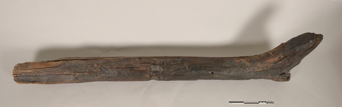 """Stevn av båt av treverk, med fem hull for jernbolter. To jernbolter bevart.  Merket med tusj som """"III-23""""."""