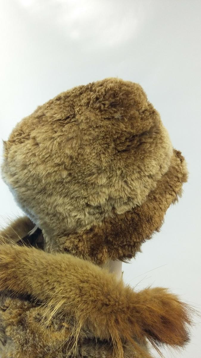 Lue. Pelskledd på utsiden og på innsiden langs bremmen. Foret med vattert forsilke på innsiden. Både for og pels er litt slitt.
