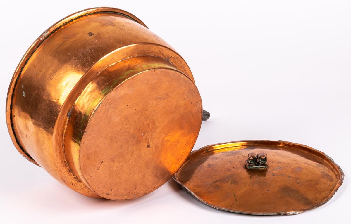 Kastrull, koppar, med lock och skaft. Mått: a) h 11.5cm, diam, 19cm (kastrull). b) diam 8,5 cm (lock). Från 1800-talets senare del.