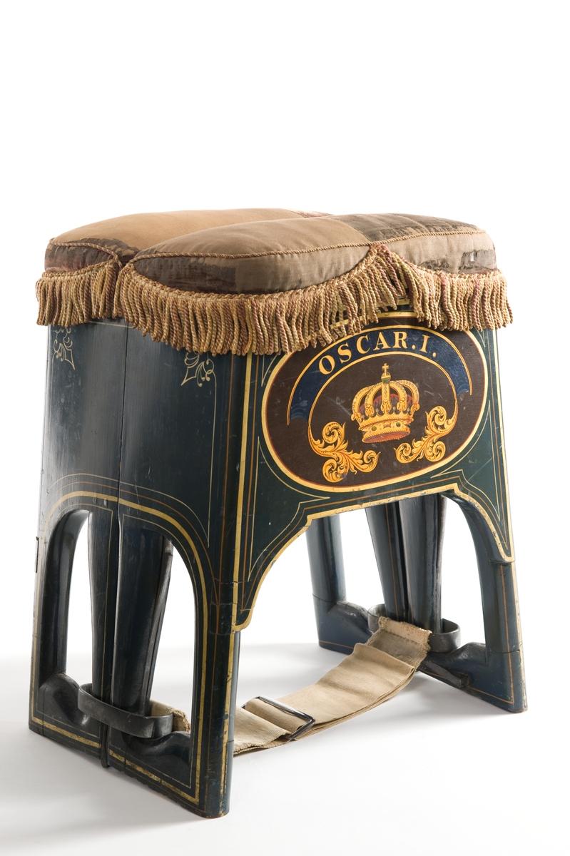 """Livräddningstol, märkt: """"Patent. Folding life - preserving seat, invented by Nathan Thompson j:or, New York, 1853"""", hopfällbar och monterad som taburette. Sitsen är av violette sammet med fransad kant. Stolen är blåmålad och dekorerad med Kunglig krona och däröver """"Oscar I"""" samt svenska och amerikanska vapnen med Kunglig krona och dubbelörnen över."""