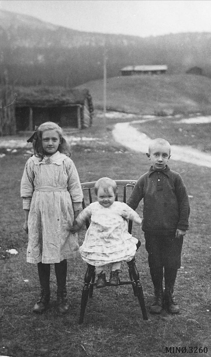 En liten gutt, ei lita jente, lillesøstera deres på en stol. Sjarm