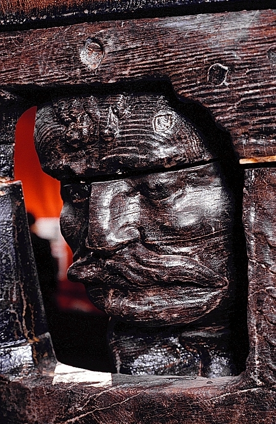 """Skulpturen föreställer en hopkrupen mansfigur, inplacerad eller instängd i ett trångt och lågt, burliknande utrymme. Utrymmet kan beskrivas som ett ett övre, relativt tunt och platt parti som tjänstgör som ett slags tak samt ett undre parti som utgör golv. Väggar saknas. """"Tak"""" och """"golv"""" är inte parallella med varandra utan """"taket"""" är riktat snett uppåt mot skulpturens främre ända. Detta ger skulpturen en kilformig profil.  """"Taket"""" och """"golvet"""" har en romboidformad plan och förbinds med varandra genom fyra ornerade stöttor som tycks bära upp """"taket"""".  I bakre ändan är stöttan ersatt av en stor dubbelsidig ros, placerad i skulpturens längdriktning.  Mannen ligger på knä och vilar framkroppen på de böjda armarna. Han är placerad på ett sådant sätt att han tittar ut genom en, på höjden, rektangulär """"glugg"""" som bildats av de två stöttor som förbinder den ena av """"golvets"""" och """"takets"""" bägge kortsidor.  Stöttorna, av vilka den yttre är delvist bortbruten, vilar nedtill på ett snett placerat och välvt bröstvärn eller dylikt. Detta är beläget framför mannen och prytt med en stor ros och ritsade spiraler.  Mannen ryms med nöd och näppe i det trånga utrymmet. Han måste ha både knän och armar utanför stöttorna som uppenbarligen trycker hårt mot hans kropp.  Han har ett grovt, fyrkantigt ansikte med håret neddraget i pannan, klumpig näsa och stora, långsträckta mustascher men saknar skägg.  Han är iförd en """"civil"""" dräkt, en långärmad, rikt veckad klädnad som troligen når ned till strax nedanför knäna. På fötterna har han kängliknande skor.  Skulpturen är snidad runt om och kan studeras från alla fyra sidor. Genom den romboidformade grundplanen har skulpturen fyra sidor, förutom över- och undersida. Den ena långsidan och kortsidan svarar mot vänstra sidan av mannens kropp respektive ansiktet och bröstvärn- skulpturens framsida. Den andra långsidan och kortsidan svarar mot mannens bakhuvud och högra sida av bålen, respektive ben och fötter- skulpturens baksida.  Mannens huvud är """