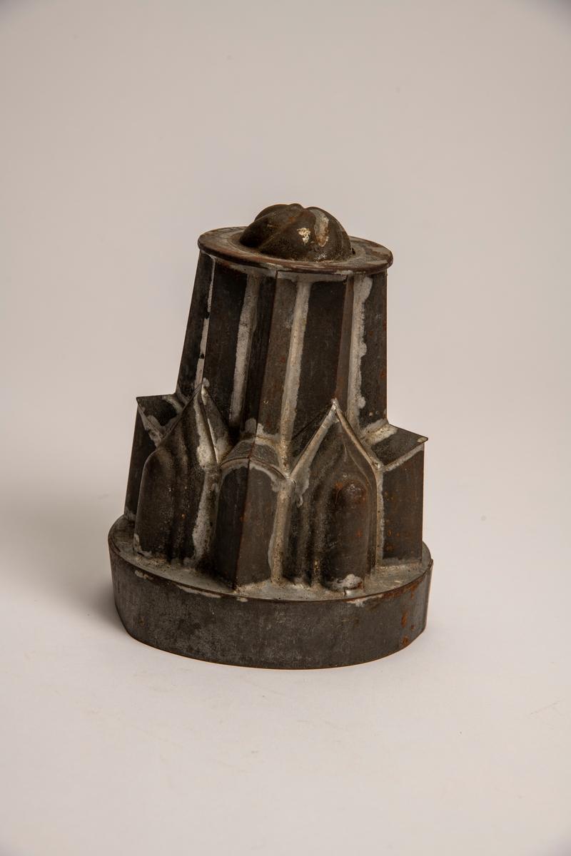 Pyramidal hovedform med rundet bunn med svungne riller, takket nedre konstruksjon.