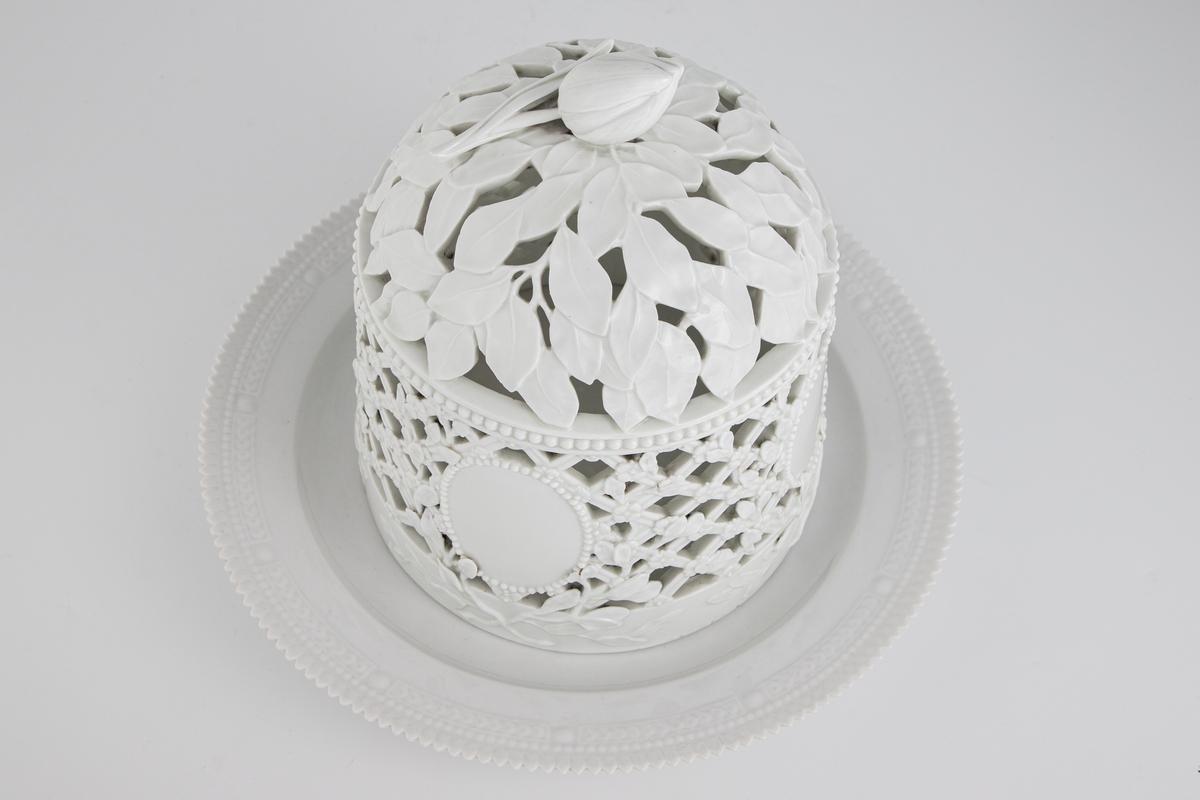Isklokke med fat i hvitt porselen. Isklokken er uten malt dekor. Veggene i klokken er i åpen kurvdekor ned små blomster. Medaljong i fronten omgitt av blomsterranker. Perlebånd på toppen av korpus. Avrundet topp med plastiske blader og tullipan.